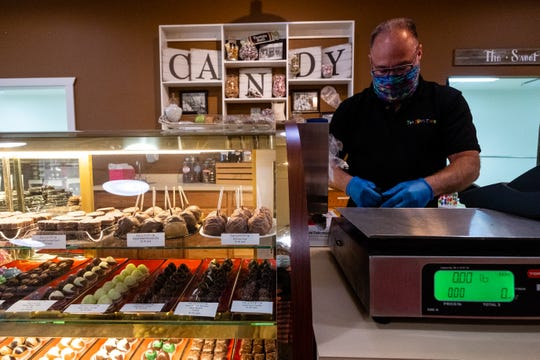 Todd May, owner of The Sweet Tooth in Marine City, works to package a box of assorted chocolates being presented as a gift Thursday, May 14, 2020, in Marine City. When it is able to reopen to customers again, May plans to offer customers gloves and masks when they enter the store.
