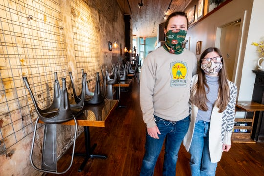 Maggie and Nathaniel Bottenfield, owners of the Exquisite Corpse Coffee House, pose for a portrait next to chairs stacked on tables Thursday, May 14, 2020, in Port Huron. The chairs are stacked and the couches have been reversed to discourage guests from hanging out while the coffee house is doing carryout orders due to the coronavirus pandemic.