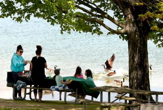 """Laurie Bosley, left, and Brittany Miller, both of New Freedom, talk while having a picnic with their children at Codorus State Park Thursday, May 14, 2020. """"We haven't seen each other for two months,"""" Miller said. The mothers decided on an outdoor setting for the get-together. Bill Kalina photo"""