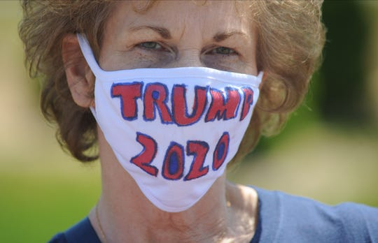 Marybeth Zelinka of Hanover, Pennsylvania wears a Trump 2020 mask along with other supporters gathered across the street from a facility the President was touring  Thursday, May 14, 2020 in Uper Macungie. The parade was put together by the local community with the help of a former elementary school teacher. (WILLIAM THOMAS CAIN/PHOTOJOURNALIST)