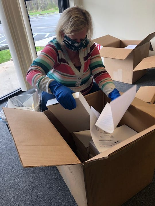 A volunteer with Jeannie's Fund unpacking purchased iPads. Volunteers clean, test and label the devices before they go out to hospitals or other facilities.