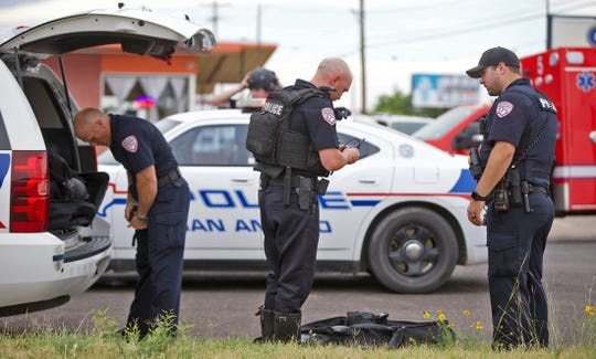 Members of the San Angelo Police Department SWAT team, far left and center, put on special equipment at the scene of a standoff at a house on East 20th Street on Wednesday, May 13, 2020.