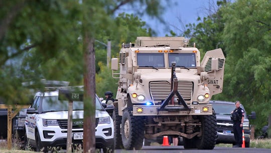 An armored SWAT team vehicle stands by at the scene of a standoff at a house on East 20th Street on Wednesday, May 13, 2020.