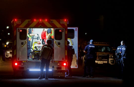 A suspect is loaded into an ambulance, seen at far left, at the scene of a standoff at a house on East 20th Street on Wednesday, May 13, 2020.