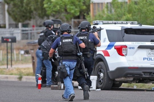 Members of the San Angelo Police Department SWAT team move into position at the scene of a standoff at a house on East 20th Street on Wednesday, May 13, 2020.