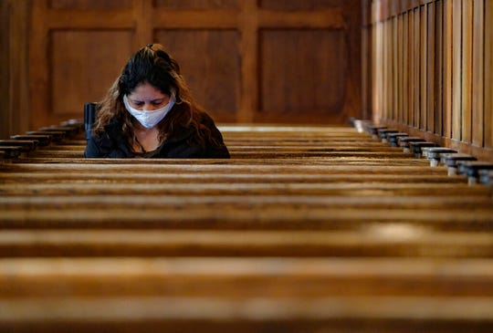 A Catholic parishioner observe morning daily Mass at the Cathedral of the Madeleine in Salt Lake City, Friday, May 8, 2020, where a majority of the pews are taped off due to restrictions implemented to combat COVID-19. (Francisco Kjolseth/The Salt Lake Tribune via AP)
