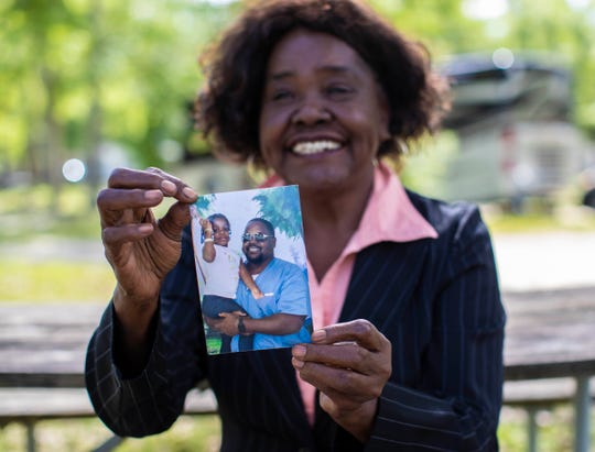Inez Williams-Jones sits outside on the Tallahassee Campgrounds while holding a photograph of her son Marshall Williams and his daughter Martierria Williams, 3. Marshall, who is Muslim, is celebrating Ramadan while incarcerated at the Gadsden County Jail.