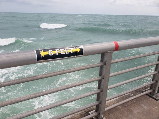 The railings at Sebastian Inlet State Park's north jetty instruct anglers to abide by social distancing practices.