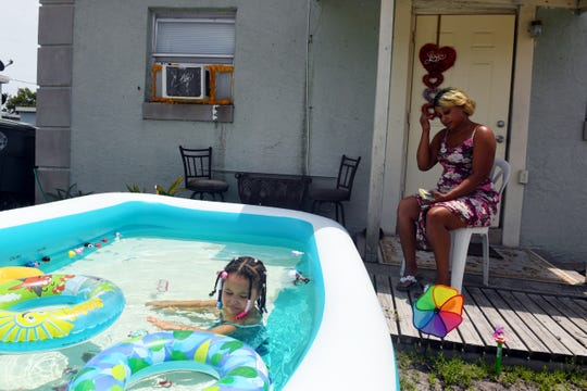 Ebony Rowe sits on the front porch of her Fort Pierce home while her daughter, Honesty, 4, plays in an inflatable pool on Thursday, May 14, 2020, in Fort Pierce. Because of the COVID-19 pandemic, Rowe had to leave her job as a home health worker to care for her daughter who has a congenital lung disorder and cannot attend her regular daycare. Rowe received a phone call from her landlord stating that because she was out of work, she would be served an eviction notice and be required to vacate the premises in three days.