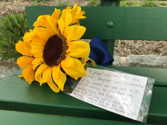 A visitor to the Delaware Veterans Memorial Cemetery leaves a flower with a note for Paul and Lidia Marino's family members. The elderly couple was gunned down there on May 8.
