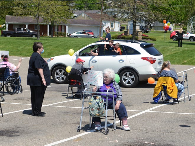Residents sit in the parking lot of Continuing Healthcare at Willow Haven during a parade on Wednesday in Zanesville.