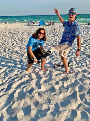 Sebastian Morris attaches Carter Hess's artificial leg out at Panama City Beach on Tuesday. The teenager recently found the leg, which Hess lost last month ago surfing, while diving in St. Andrews State Park.