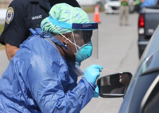 Shandrika Pritchett with the Walton County Health Department administers a COVID-19 test at a drive-thru testing station set up at the Van R Butler Elementary School on May 14 in South Walton County, Fla.