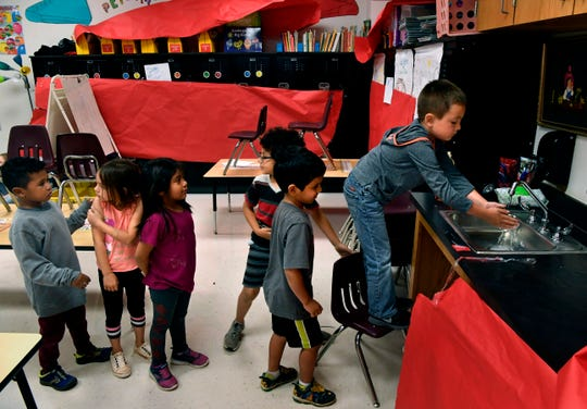 Children line up to wash hands before lunch at a daycare held at Martinez Elementary School in Abilene, Texas Wednesday April 1, 2020. The child care is organized by United Way of Abilene and is being provided at no cost for essential workers.