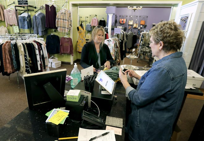 Lillians of Appleton owner Kara Manuel  helps Sandy Sonsthagen with her purchases in the downtown Appleton store.