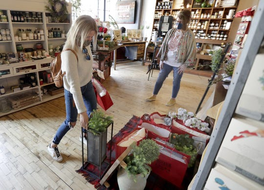 Melinda Cranwell, left,  picks up an order from owner Tina Palmer at Red Door Mercantile in Neenah.