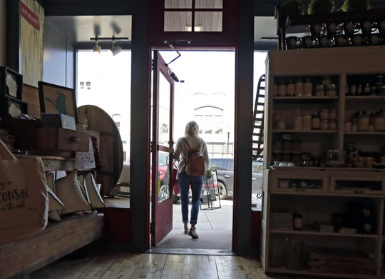 A customer picks up an order curbside at Red Door Mercantile in Neenah.