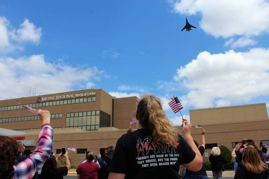 """Shirley Taylor, center, who works with employee health at Abilene Regional Medical Center, raises her flag to wave as a Dyess-based B-1 bomber suddenly appears over the south Abilene hospital Friday afternoon.  """"It's really cool,"""" she said of the military appreciation moment for healthcare workers and first responders across Abilene. May 15 2020"""