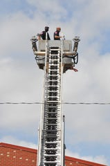 Two Abilene Fire Station 1 crew members watch Friday from the extended ladder truck bucket for the Dyess Air Force Base flyover to honor first responders and hospital workers on the front lines of the COVID-19 pandemic.