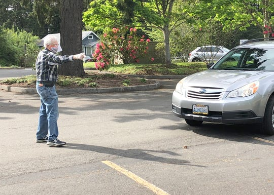Parking attendant David Swartling directs vehicles at a drive-in worship service at Bethany Lutheran Church of Bainbridge Island on May 9.