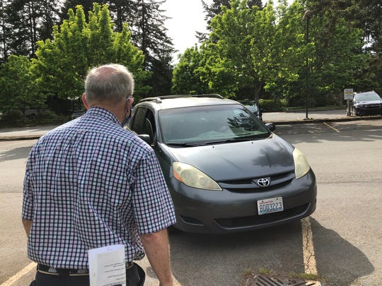 Parking attendant Jim Rohrscheib directs cars into the lot at Bethany Lutheran Church of Bainbridge Island prior to a drive-in worship service on May 9.