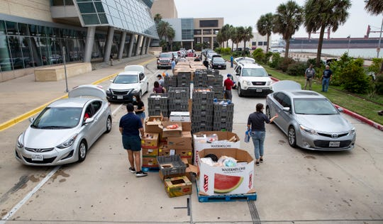 People drive to American Bank Center to get food from a 'pop-up' food bank on Friday, May 15, 2020. The food giveaway was organized by the Coastal Bend Food Bank and the city of Corpus Christi.