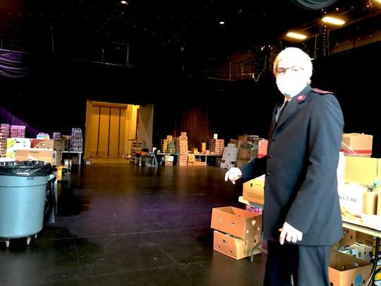 Major Terry Wood, administrator of the Salvation Army Kroc Center in Camden, shows how the facility's black box theater has been transformed into a makeshift food bank.
