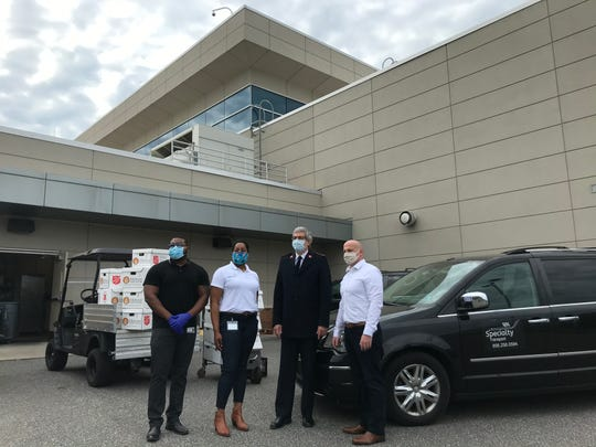 Anthony Jones (left to right), Ashley Wright, Major Terry Wood and Jamie Moses stand outside the Salvation Army Kroc Center in Camden as trucks are loaded with boxes of food for those in need.