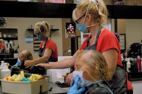 Kelli Lackman cuts a customer's hair, name not given, at Hairline 1 Nailcrafters during their first day back open on Friday, May 15, 2020 in the Cincinnati neighborhood of Finneytown.