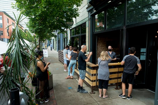 Patrons stand around Bakersfield on Friday, May 15, 2020, in Over The Rhine. Friday marked the first day restaurants could serve in outdoor spaces since restriction on restaurants were put in place in mid March due to the new coronavirus pandemic.