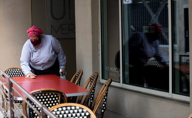 Seagal Zaid, The Mercer manager, cleans a table in Over The Rhine. May 15 was the first day restaurants could serve in outdoor spaces since restriction on restaurants were put in place in mid March due to the coronavirus pandemic.