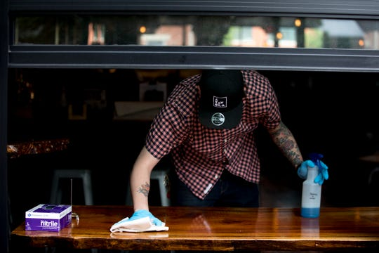 An employee at A Tavola Bar and Trattoria cleans off a table on Friday, May 15, 2020, in Over-the-Rhine. Friday marked the first day restaurants could serve in outdoor spaces since restrictions were put in place in mid March due to the new coronavirus pandemic.