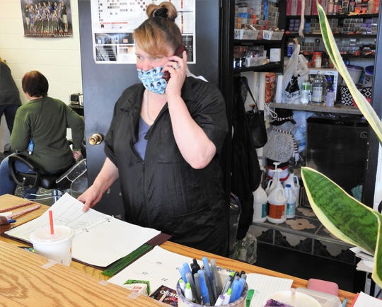 Charlene Hixon of Sensational Styles takes an appointment by phone on Friday. Hixon said the phone has been ringing almost non-stop with people wanting to book appointments and they're currently booking about a week in advance right now.