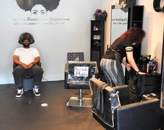 Jason Byrom of Newcomerstown sits under a dryer while stylist Jordan Wilkinson cleans up from her last customer at Namaste Hair Salon in Newcomerstown. The business started taking customers again by appointment only on Friday after pandemic closures ordered by the state.