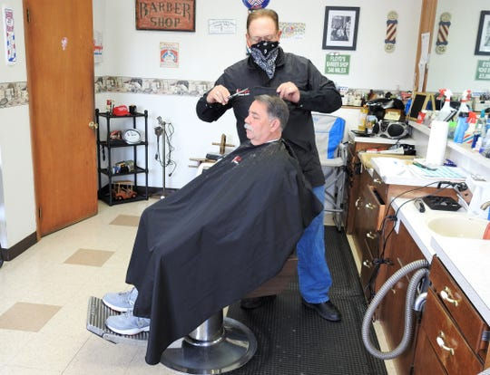 Lenny Fowler of Lenny's Barbershop cuts the hair of Rob Ford on Friday. It was the first day barbershops and salons could reopen for business while observing new mandates, like employees wearing masks and clients able to come in by appointment only.