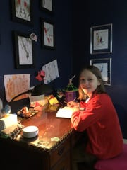 """Xan Clarkson, 10, of East Lansing is shown in a photo submitted to the Michigan History Center's """"COVID-19 Collecting Initiative. """"In my free time, I get to do a lot of art,"""" she said in the caption."""