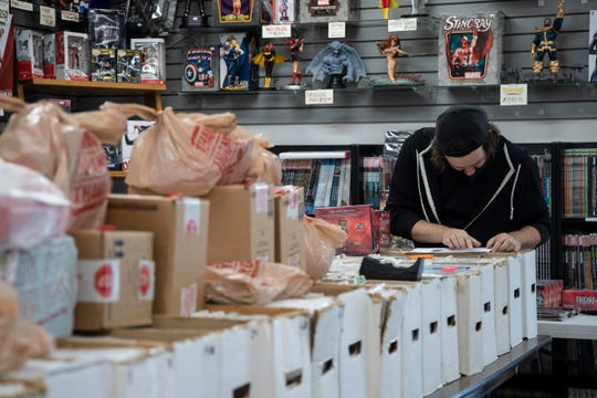 Stadium Cards & Comics employee Michael Atkinson fills an order for curbside pickup in the store in Ypsilanti, Friday, May 15, 2020.