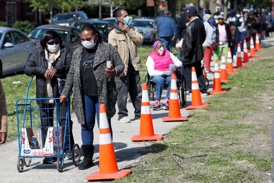 In this Tuesday, May 12, 2020, photo, residents from all walks of life line up for a food giveaway sponsored by the Greater Chicago Food Depository in the Auburn Gresham neighborhood of Chicago.