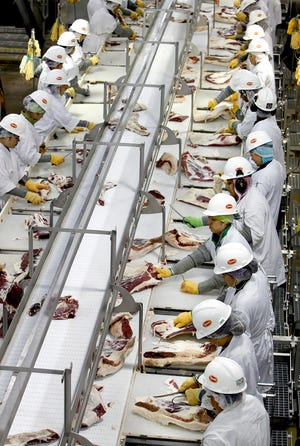 Workers trim beef at the Tyson Fresh Meats plant in Dakota City, Neb. in 2012. (Keith Myers/Kansas City Star/TNS)