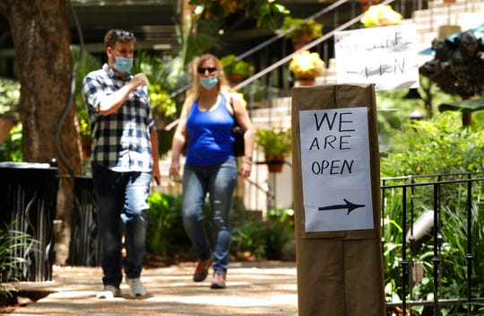 People wearing a face masks for protection against COVID-19 pass a business that has reopened in San Antonio, Thursday, May 14, 2020.