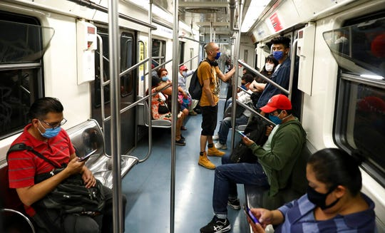 Commuters wearing masks against the spread of the new coronavirus ride the subway in Mexico City, Thursday, May 14, 2020.
