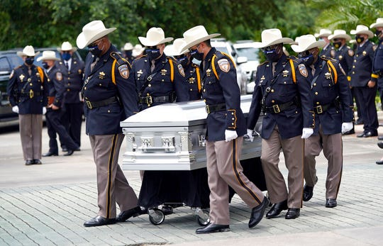 Members of the Harris County Sheriff's Honor Guard move the casket during a funeral service for Sgt. Raymond Scholwinski Thursday, May 14, 2020, in Humble, Texas. Sgt. Scholwinski died last week after contracting COVID-19.
