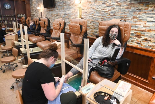 COVID-19 survivor Nawal Hamade of Temperance, Michigan, enjoys a pedicure at EsprŽs Nail and Salon in Toledo, Ohio by nail tech Hailey Willey on Friday, May 15, 2020.