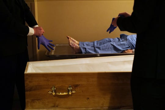 Pallbearers, Louis Mercier, right, and Allan Pottier, left, prepare to carry the body of a 105-year-old woman as they prepare her for funeral at a mortuary, in Paris, Friday, April 24, 2020, as a nationwide confinement continues to counter the COVID-19 virus.