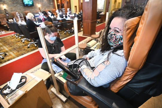 COVID-19 survivor Nawal Hamade of Temperance, Michigan, enjoys a pedicure at EspresNails & Spa in Toledo, Ohio, by nail tech Hailey Willey on Friday, May 15, 2020.