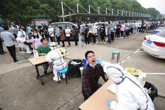Workers line up for medical workers to take swabs for the coronavirus test at a large factory in Wuhan in central China's Hubei province Friday, May 15, 2020. Wuhan have begun testing inhabitants for the coronavirus as a program to test everyone in the Chinese city of 11 million people in 10 days got underway.