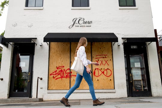 In this April 29, 2020, file photo, a woman walks past a boarded up J. Crew storefront along 14th Street in Northwest Washington.