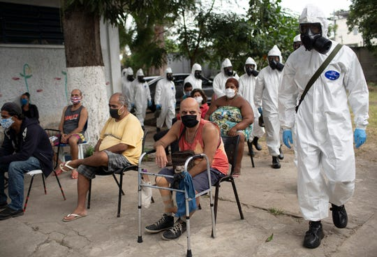 Elderly residents listen to music as soldiers in full protection gear against COVID-19, arrive to disinfect the Complex Stella Maris shelter for the elderly in Rio de Janeiro, Brazil, Thursday, May 14, 2020. Soldiers disinfected the shelter in an attempt to control the spread of the new coronavirus among the elderly who are part of the group considered more vulnerable or at risk of being infected.