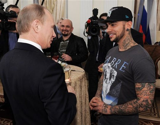 Russian Prime Minister Vladimir Putin speaks with Russian performer Timati during a meeting with supporters in Moscow in this March 5, 2012, file photo.