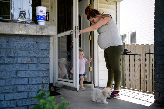 Sunny Goodman holds the door open for her 2-year-old daughter Daisy as they prepare to go on a walk around Garvin Park in Evansville, Ind., Thursday afternoon, May 14, 2020. By the end of May, Goodman is expecting to make Daisy a big sister to a new baby boy.